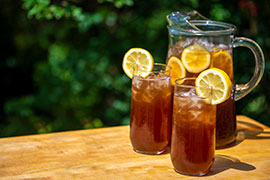 pitcher and glasses of iced tea with lemon on wood table