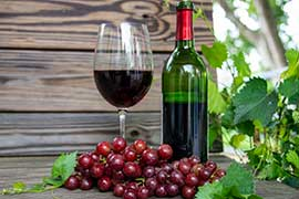 muscadine wine in glass and bottle and grapes