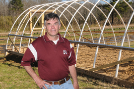 scientist in front of hoop house